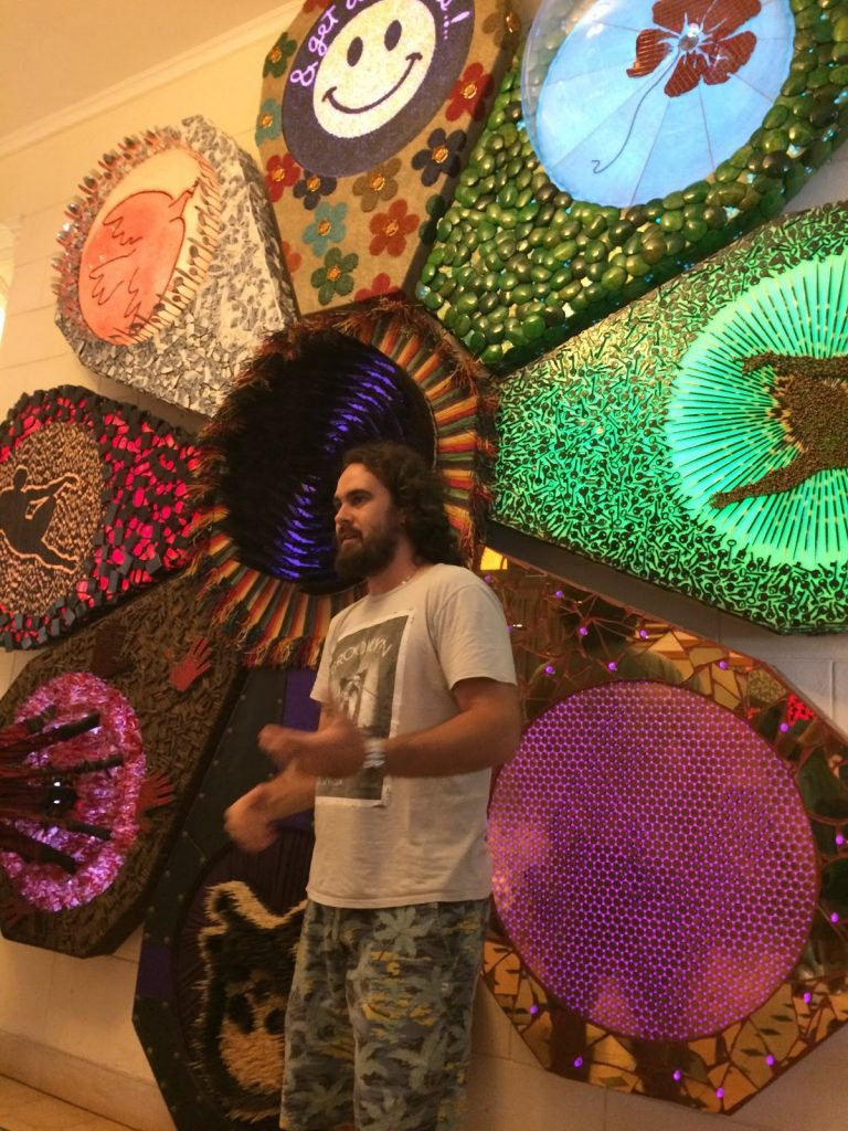"Artist Lorenzo Lopez in front of his art ""Love Me, Love Me Not"""