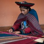 A woman at the Chinchero Weaving Collective works on a loom