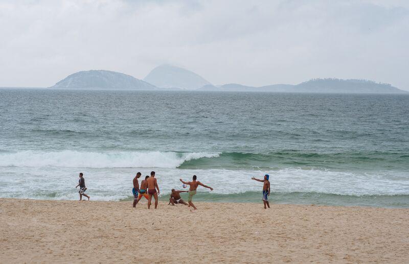 A group of guys juggling a soccer ball on Copacabana Beach