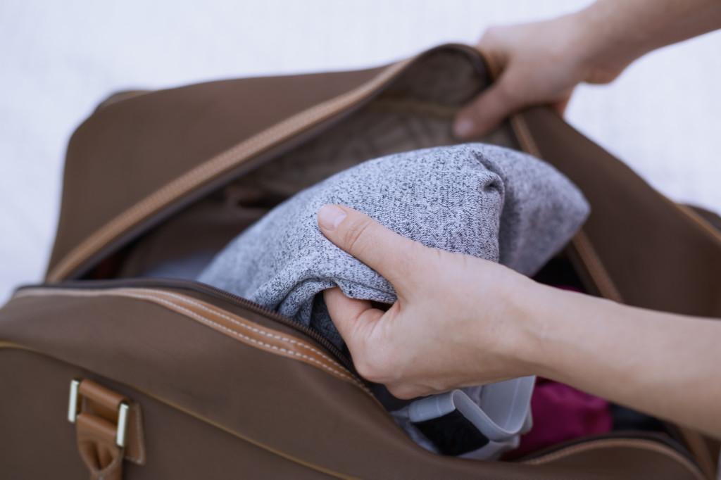 Hands of man unpachking travel bag